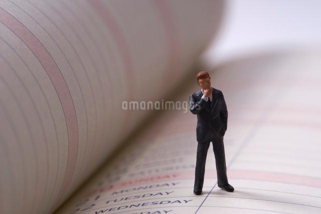 ビジネスマンのミニチュア人形とスケジュール帳の写真素材 [FYI01645512]