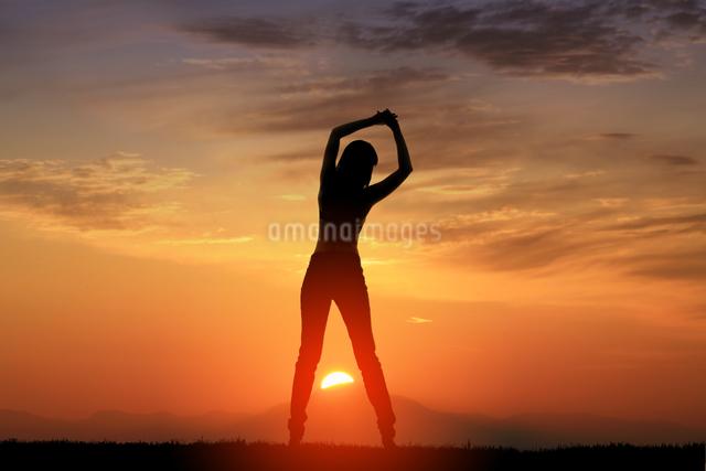 朝日と女性シルエットの写真素材 [FYI01647085]