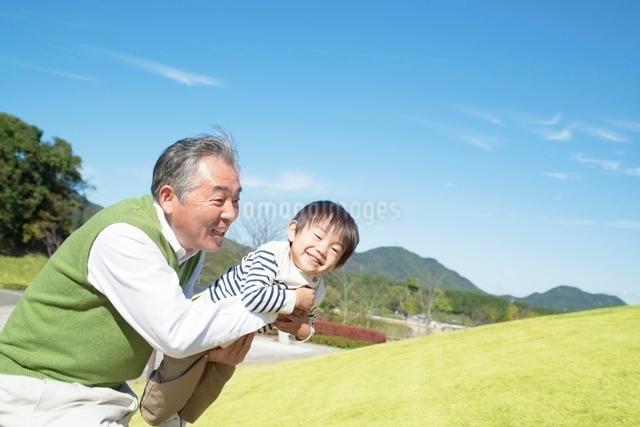孫を抱き上げる祖父の写真素材 [FYI01650424]