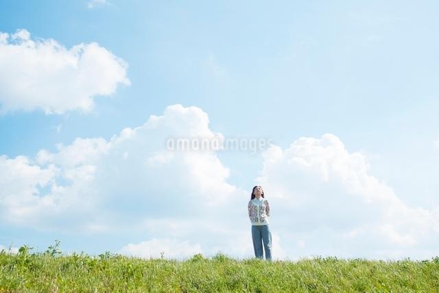 丘の上に立ち空を見上げる女性の写真素材 [FYI01650547]