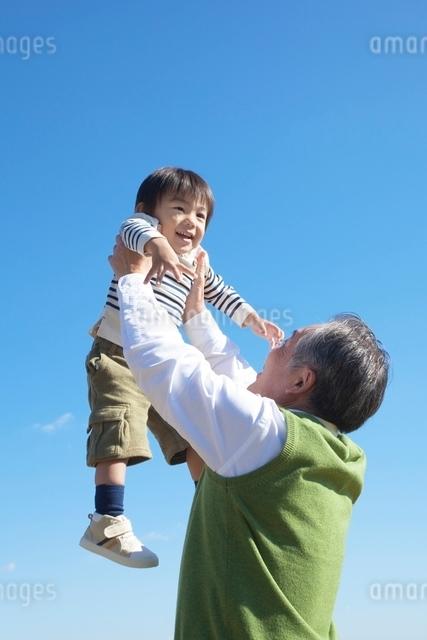 孫を抱き上げる祖父の写真素材 [FYI01650644]