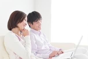 パソコンをのぞきこむ笑顔のカップルの写真素材 [FYI01650944]