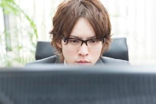 パソコンのモニターを見つめるビジネスマンの写真素材 [FYI01651091]