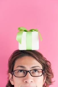 プレゼントボックスを頭の上にのせた男性の写真素材 [FYI01651526]