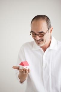家の模型を見つめる日本人男性の写真素材 [FYI01651601]