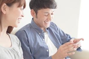 携帯電話をのぞく笑顔の日本人カップルの写真素材 [FYI01651603]