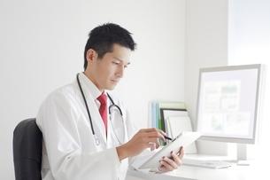 タブレットPCを操作する男性医師の写真素材 [FYI01652549]