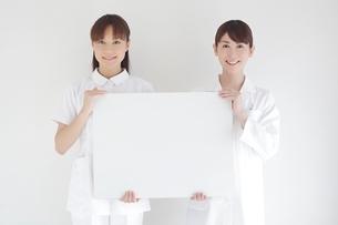 メッセージボードを持つ女性医師と看護師の写真素材 [FYI01652550]