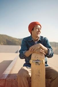 スケートボードを持つ笑顔の男性の写真素材 [FYI01652553]