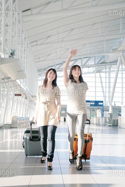 キャリーバッグをひいて歩く2人の女性の写真素材 [FYI01652693]