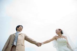 手をつなぎ見つめ合う笑顔の新郎新婦の写真素材 [FYI01653585]