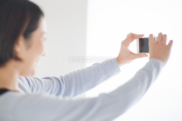 スマートフォンで撮影をする20代女性の写真素材 [FYI01653906]