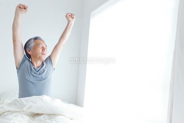 ベッドで背伸びをするシニア男性の写真素材 [FYI01654293]