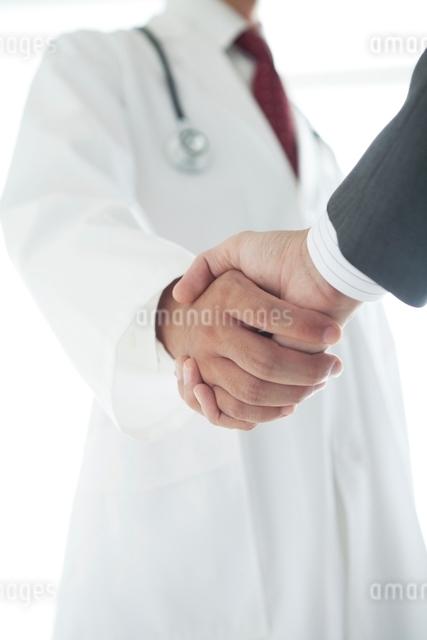 握手する医師とビジネスマンの手元の写真素材 [FYI01654306]
