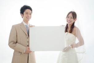 メッセージボードを持つ笑顔の新郎新婦の写真素材 [FYI01654731]