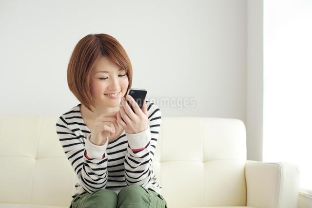スマートフォンを操作する笑顔の女性の写真素材 [FYI01654974]