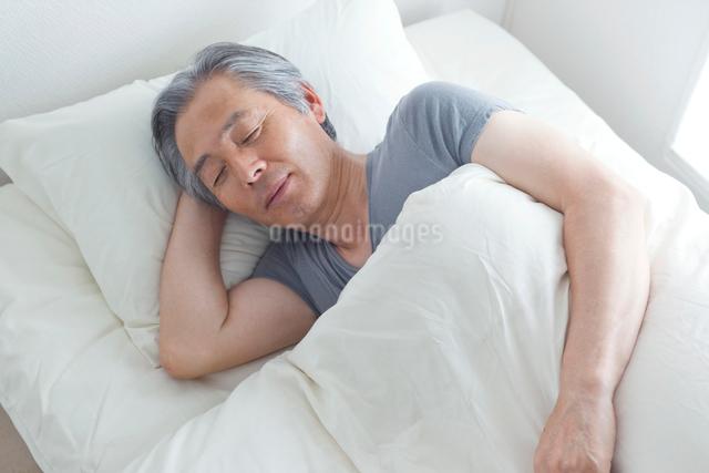 ベッドで眠るシニア男性の写真素材 [FYI01655467]