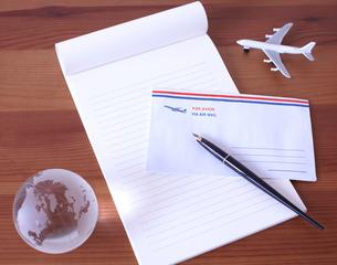 地球儀と飛行機の模型が置かれた木の机の上のエアメールと万年筆の写真素材 [FYI01665807]