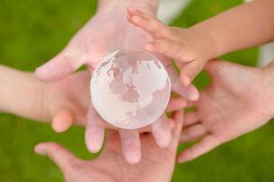 ガラスの地球を持つ祖父祖母と孫の手の写真素材 [FYI01665820]