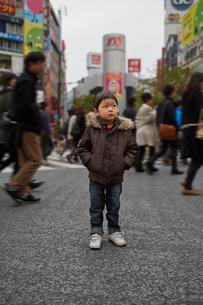 東京渋谷スクランブル交差点に悲しい顔をして佇む子供の写真素材 [FYI01665881]