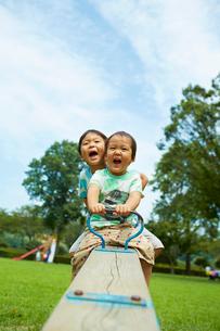 シーソーに乗って笑顔の子供と幼児の写真素材 [FYI01665894]