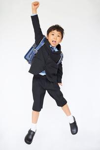 スーツで青いランドセルを背負いジャンプする小学一年生の写真素材 [FYI01665900]