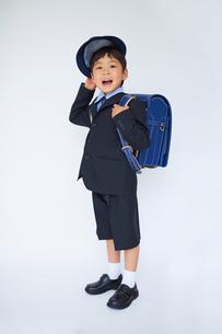 スーツで青いランドセルを背負い帽子を脱ぐ小学一年生の写真素材 [FYI01665932]