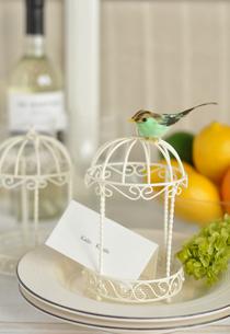 小鳥の乗った鳥籠のテーブルセッティングの写真素材 [FYI01668583]