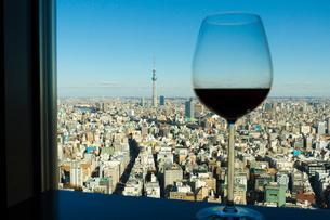 高層ビルから眺める東京スカイツリーとワイングラスの写真素材 [FYI01669190]