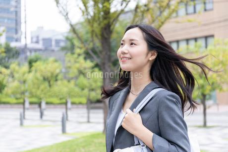 髪をなびかせ歩くビジネスウーマンの写真素材 [FYI01686333]