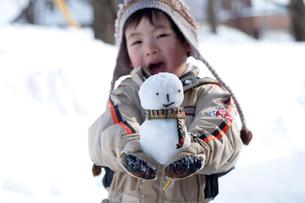 雪だるまを持つ男の子の写真素材 [FYI01687782]