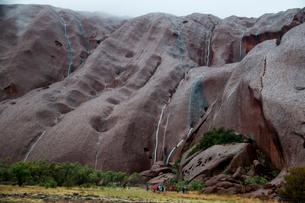 エアーズロックの岩山の岩肌をつたい落ちる雨水の写真素材 [FYI01690442]