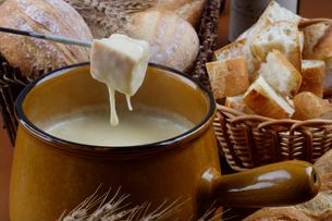 チーズフォンデュにフランスパンをつけるの写真素材 [FYI01691815]