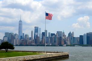 エリス島の星条旗とロウアーマンハッタンのビル群の写真素材 [FYI01693484]