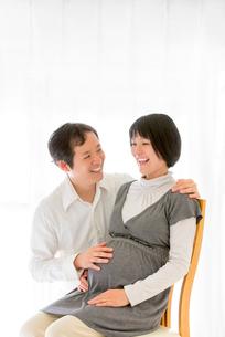 リビングでくつろぐ出産前の夫婦の写真素材 [FYI01700739]