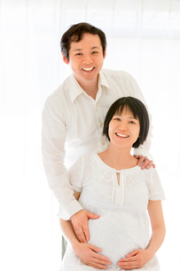 リビングでくつろぐ出産前の夫婦の写真素材 [FYI01700798]