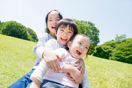 公園で遊ぶ3人兄弟の写真素材 [FYI01701181]