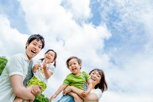 公園で遊ぶ4人家族の写真素材 [FYI01701942]