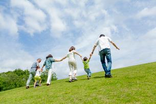 公園を手をつないで歩く3世代の後ろ姿の写真素材 [FYI01702479]