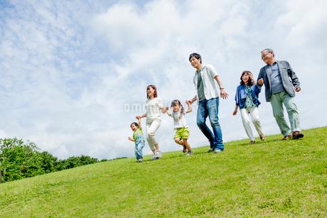 公園を手をつないで歩く3世代の写真素材 [FYI01702580]