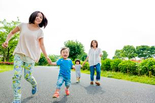 公園を歩く2組の母と子の写真素材 [FYI01702786]