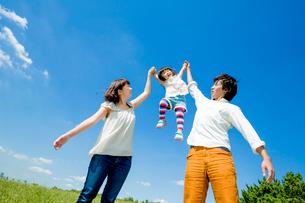 公園で娘を高く掲げる両親の写真素材 [FYI01702899]