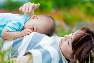 公園で母親の上で眠る息子の写真素材 [FYI01702989]