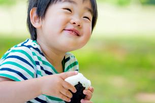 公園でおにぎりを食べる男の子の写真素材 [FYI01703153]