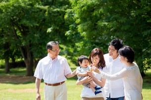 公園を歩く3世代の写真素材 [FYI01703402]