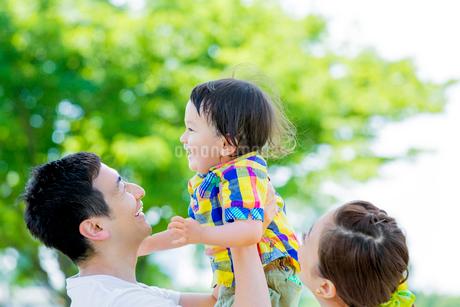 公園で息子を抱き上げる両親の写真素材 [FYI01703429]