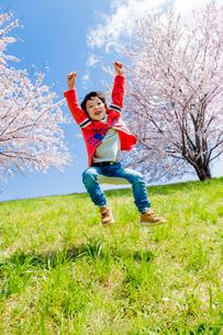桜の咲く土手でジャンプする男の子の写真素材 [FYI01703541]