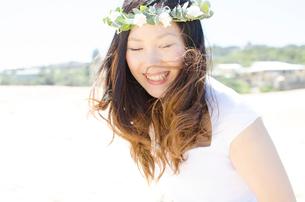 砂浜で花冠をして笑うウェディング姿の女性の写真素材 [FYI01703760]