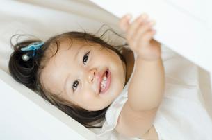 寝そべって笑顔のハーフの女の子の写真素材 [FYI01703796]