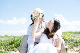 屋外に座り笑い合うウェディングカップルの写真素材 [FYI01703801]